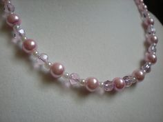 Very subtle color and shine make this a delicate piece of elegance. Light pink and white glass pearls are interspersed with light pink glass crystals. Graduated in size to create a modern classic look.    Length: 16 inches  $19.00