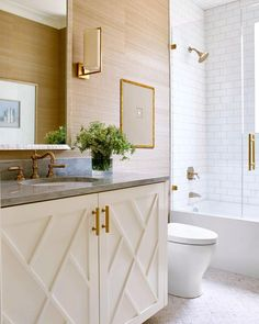 White bathroom - subway tile - brass fixtures, hardware, sconces - custom vanity details, grass cloth