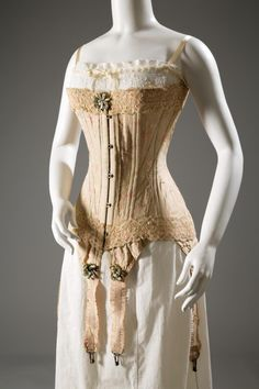 A Corset of floral brocaded silk, silk ribbon, and elastic, circa 1905, from England.
