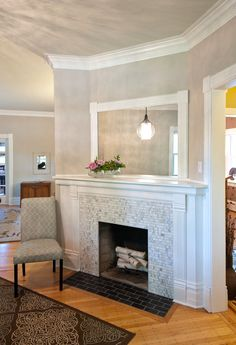 antique fire place, custom cut tile, grey walls and grey ceiling with white trim, white fireplace mantle, light blue accent chair