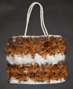 Kete, bag, made of cotton and feathers.  Kete woven with candlewick using the whatu aho rua (double-pair twining) technique; base of the bag is woven using the taniko (multi-thread twining) technique; kete has pair of plaited handles.  The two faces of the bag are decorated with brown pheasant feathers, with a central band of white feathers, attached in bunches under the aho (weft) threads.