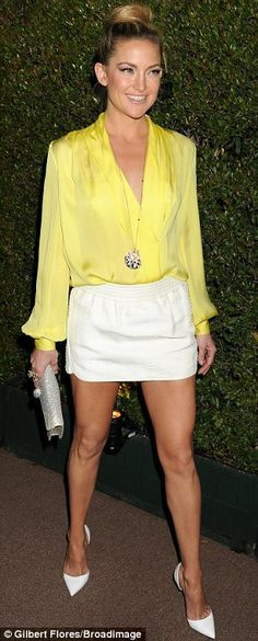 #partywear | Kate Hudson in a yellow silk V-neck blouse, an Emilio Pucci white leather mini skirt & white Christian Louboutin  pumps styled with a sparkling BVLGARI clutch