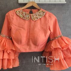 Peach blouse with ruffled sleeves and peter pan collar embellished with rhinestones Peach blouse with ruffled sleeves and peter pan collar embellished with rhinestones Choli Designs, Saree Blouse Neck Designs, Stylish Blouse Design, Fancy Blouse Designs, Bridal Blouse Designs, Designer Blouse Patterns, Collor, Indian Designer Outfits, Peter Pan Collar Blouse