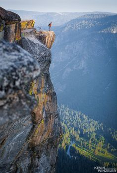 A photographer stands overlooking the beautiful valley of yosemite national park at sunrise including the icons of El Capitan and Half Dome.