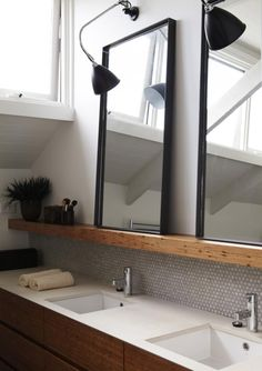 tilework + wood shelf + twin mirrors + black sconces in bathroom design