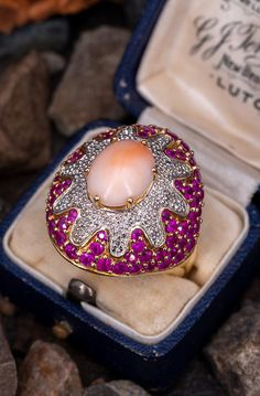 This gorgeous cocktail ring is centered with an oval, coral cabochon in a six-prong setting. The center is surrounded by thirty bead set, round brilliant cut diamonds and seventy-two prong set, round mixed cut natural rubies. The ring measures 2 Diamond Shapes, Diamond Cuts, Pink Sparkly, Aquamarine Jewelry, Pink Ring, Brilliant Diamond, Cocktail Rings, Thirty 30, Prong Set