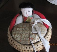 ABSOLUTELY LOVE THIS DARLING BOY CHILD.. gofun face, black bowl cut hair do.. and nestled in a vintage wicker basket and the front would be a pin cushion.. love this old wicker basket.. and there is a bobbin type thing hanging from the ribbon as well... from base to top of boy child's head about 3 inches high. and the width across is just under 4 inches.... the bobbin thingy is made of painted wood I believe.. good home for this hard to find wonderful Oriental doll pin cushion.., cutest…