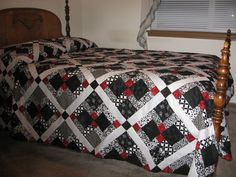 Black white and red quilt disappearing 9 patch. Center square is red, the 4 corners are black and the rest are black/white. Sashing in white with black corner stones.