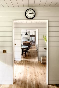 Knotty oak flooring runs throughout much of the house, uninterrupted by doors. The clock is from Schoolhouse.