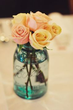 Roses in a Mason Jar...kinda like this but with purple and blue marbles and white carnations.