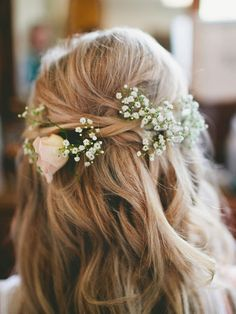 Loose bridesmaid hair fastened with messy baby's breath is a fresh way to bring flowers into your wedding look.