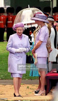 Queen Elizabeth Ll Walking Past Princess Diana At The Unveiling Of The Canada Memorial Foundation Monument In Green Park, London. Both The Queen And The Princess Are Dressed In Mauve-coloured Suits For The Occasion.