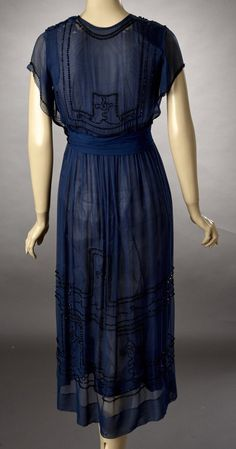 1920s Early 20s deep teal silk Georgette dress with black beading. The skirt is lined in silk organza, which is splitting. The bodice is lined in China silk.The dress snaps close across the left shoulder and on the left side seam. Inner waist tape band supports the weight of the dress. The beading is set in a geometric design. Back
