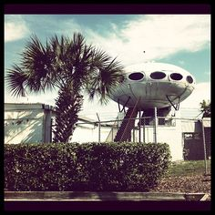 Original Futuro house, perched in perpetually tragic ignominy atop a strip club in Tampa, FL. The prefabricated fiberglass Futuro houses were designed and built in 1968 by Finnish architect Matti Suuronen, meant to be the easily-built-and-deployed homes of the future. An estimated 50 of them survive around the world. I don't know if this one counts...