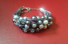 Bransoletka z szarego sznurka woskowanego ze szklanymi perełkami: srebrnymi, białymi i błękitnymi.