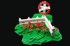 Lego Remembrance Memorial.  To make the perfect Lego circle, attach flowers to clips & attach to flex hose.  Tighten circle and insert 2 flags.  (the planted flowers are from the new Lego friends sets)