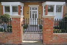 Stylish black cast iron gate with red brick posts in front garden.
