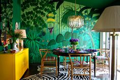 A stylized, almost surreal jungle mural covers one wall of a zebra-rug-lined dining area in the Los Angeles home of M. Design Interiors principal Molly Luetkemeyer. The 1950s post-and-beam residence is among the few non-European projects included in the book. Photo courtesy of M. Design Interiors, Inc.