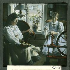 """""""F.12. Setesdal infr. Spinning"""", HÃ¥ndkolorert dias. To kvinner i hvit Setesdalsstakk karder ull og spinner garn med rokk av typen hjulrokk eller spinnrokk. Fotograf: Wilse, Anders Beer"""