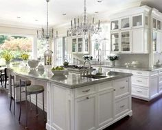Large island, wrap around white cabinets, dark floors