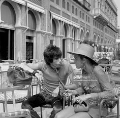 English musician Keith Richards talking to Anita Pallenberg, sitting outside the Excelsior Hotel, Lido, Venice, 1967.