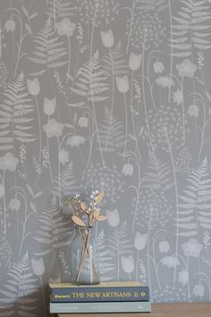 Charlotte's Garden in 'mist', a soft grey, by Hannah Nunn - a wallpaper inspired by the flowers in bloom in the Brontë Parsonage garden around the time of Charlotte Brontë's birthday. It features ferns, alliums, forget-me-nots, hellebores, fritillaries and tulips. A beautiful surface pattern design of spring flowers. Shown here with some Anna Wiscombe flowers and the new artisans book. https://www.hannahnunn.co.uk/collections/wallpaper