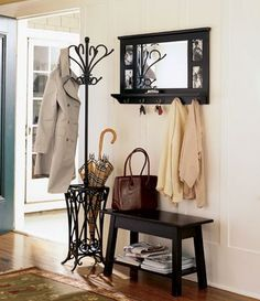 Small entryway ideas - a mirror with coat hooks above a small table or bench
