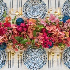 Blue and white place settings with flowers in shades of pink, rose and blue.