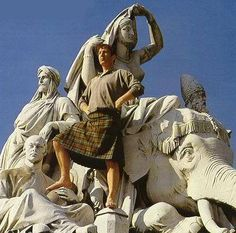 The Rickman, in kilt, on the Asia statuary group of the Albert Memorial... barefoot out of respect? (It's a good climb up there)