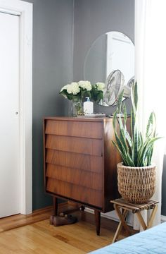 MCM dresser with mirror and greenery from Marti & Jarrod's Graphic Modern Home House Tour | Apartment Therapy