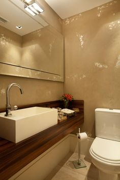 Lavabo rico em detalhes decoração. Tampo em marcenaria e paredes com pintura artesanal em fendi e prata inspiram o decor. Projeto de reforma e design de interiores em apartamento de 180m2, Moema, São Paulo.