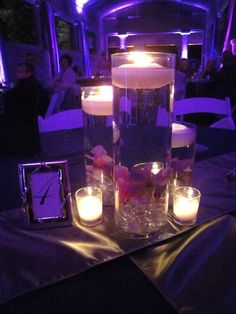 Cylinder vases with purple water and candles.  Pretty and budget friendly!