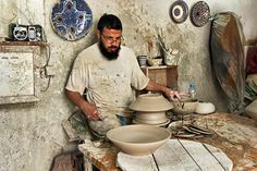 Artisan throws pottery by hand in a ceramic factory in Fez, Morocco