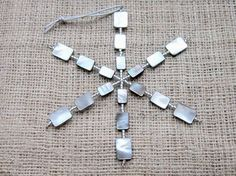 This Christmas tree decoration has been hand-beaded with a selection of black-lipped Mother of Pearl shell and seed beads onto a strong metal wire frame. The snowflake is approximately 5.5x4.75 (140x120mm), and is suspended from a knotted silver cord. Aftercare: the snowflake will need to be wrapped safely for storage, and not squashed or dropped
