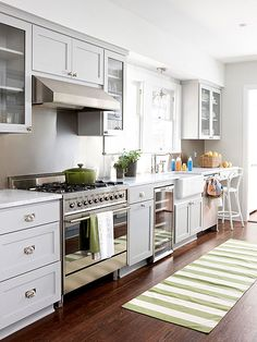 Like the pale gray cabinets, dark floor, and white farmhouse sink.  Like the white marble counters.  Would probably add white subway tile backsplash with glass accent tiles and very light blue walls and yellow accents.