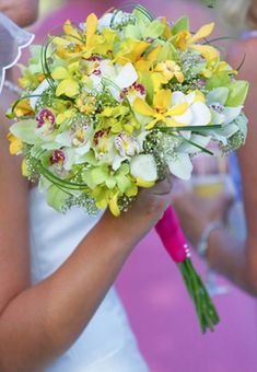 White and green cymbidium orchids, yellow orchids, small green dendrobium orchids, bear grass, babies breath and a hot pink ribbon