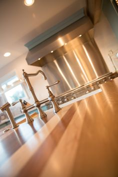 """A country farm blue kitchen with cream island. Lenova Stainless Steel Sink Faucet with Side Sprayer SK300. Cutting board countertop island. Vent-A-Hood. Wolf 60"""" Dual Fuel Range - 6 Burners, Infrared Charbroiler and Infrared Griddle with Vent-A-Hood in a blue kitchen on a Nashville, TN farm."""