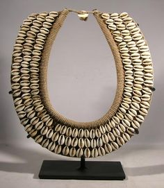 Custom display stand for an antique woven fiber and cowry shell necklace from the Sepik River region of Papua New Guinea.