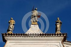Photo made at the church of St. Nicholas which is located together with the castle in the village of Strassoldo Friuli (Italy). In the picture you see the upper part of the church with the three statues that stand in the blue sky that looks like a blue cloth. The statue at the center depicts the archangel Gabriel who, with sword in hand, crushing the devil, to his right is the statue of St. Peter.