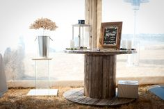 Rustic wedding. Present table. Wooden cable drum. instagram tag request. Tin buckets, Glass plinth. Handmade paper flowers. Rustic Wedding Presents, Tin Buckets, Cable Drum, Wedding Wishes, Diy Table, Wedding Table, Paper Flowers, Drums, Lanterns