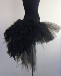 Beautiful black tutu skirt with feathers 10 12 ins long at the front with a long bustle at the back these skirts are handmade in the U.K.