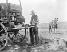 The photographer, Erwin E. Smith, stopping at the chuck wagon for a cup of coffee. LS Ranch, Texas, 1907