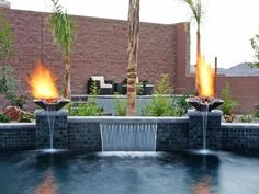 Surrounded by palm trees, fire and a small waterfall, this stunning pool is simply a tropical paradise. Paragon Pool's signature WetFlame combination water vessels and fire elements placed on raised pedestals bookend the water feature. Backyard Pool Landscaping, Backyard Pool Designs, Swimming Pools Backyard, Swimming Pool Designs, Modern Landscaping, Swimming Pool Waterfall, Tropical Pool, Tropical Paradise, Moderne Pools