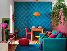 Uma parede azul, outra framboesa. Lustre laranja, sofá turquesa, banquinho amarelo, almofada pink... E não é que essa explosão de matizes conseguiu passar longe do caos, resultando em um efeito harmonioso e acolhedor. Projeto de Adriana Yazbek.