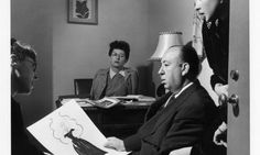 "Edith Head showing Alfred Hitchcock a sketch for Ingrid Bergman's costume for ""Notorious"". 1946"