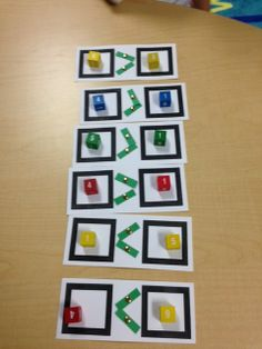 Comparing numbers using dice and greater than or less than symbols with brass brads
