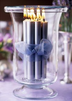 <3 Blue violet tapers held with lavender ribbon in a vase