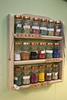 spice rack.... Me: I'm not into the Scrabble tiles but I do like the idea of using a spice rack for containing some smaller collections of bottles and such on in the office / design studio