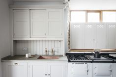 Pierced wood interior shutters, sliding upper cabinet doors, brass faucets, bead board, limestone bench top, copper sink, white Aga in a Dorset farmhouse kitchen by Plain English