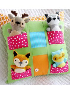 """The house pillow is fun and simple to make and great for any little one in your life! The front is made from fabric rectangles; the pockets are made separately and then whip-stitched on 3 sides to the pillow front. Cotton fabrics were used to make the sample pillow. Shown softies patterns sold separately. Size: 16"""" x 16"""". Skill Level: Easy"""